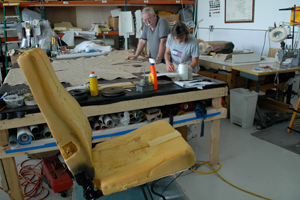 A dismantled seat waits for a new covering of leather.